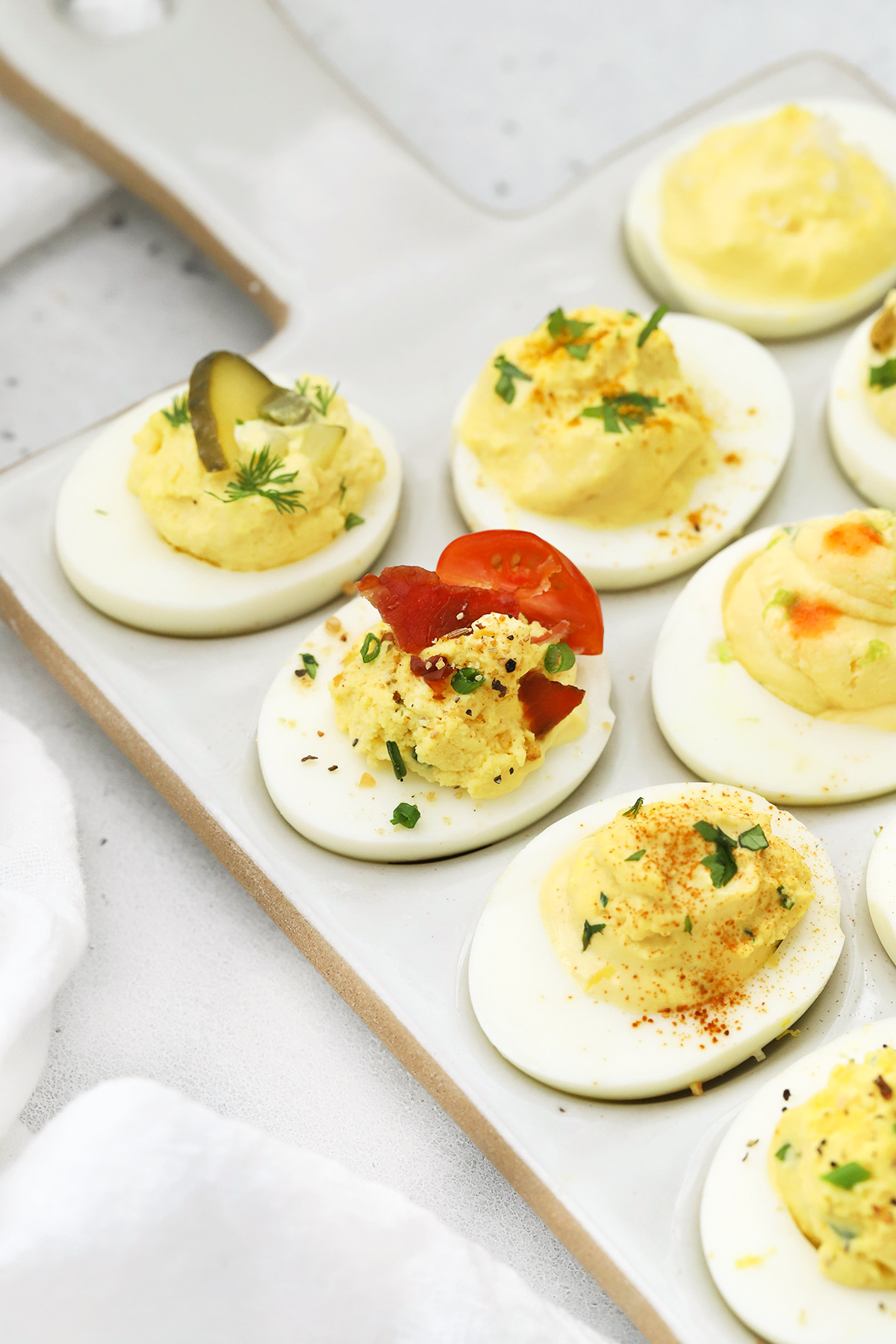 Front view of different flavors of deviled eggs on a white platter
