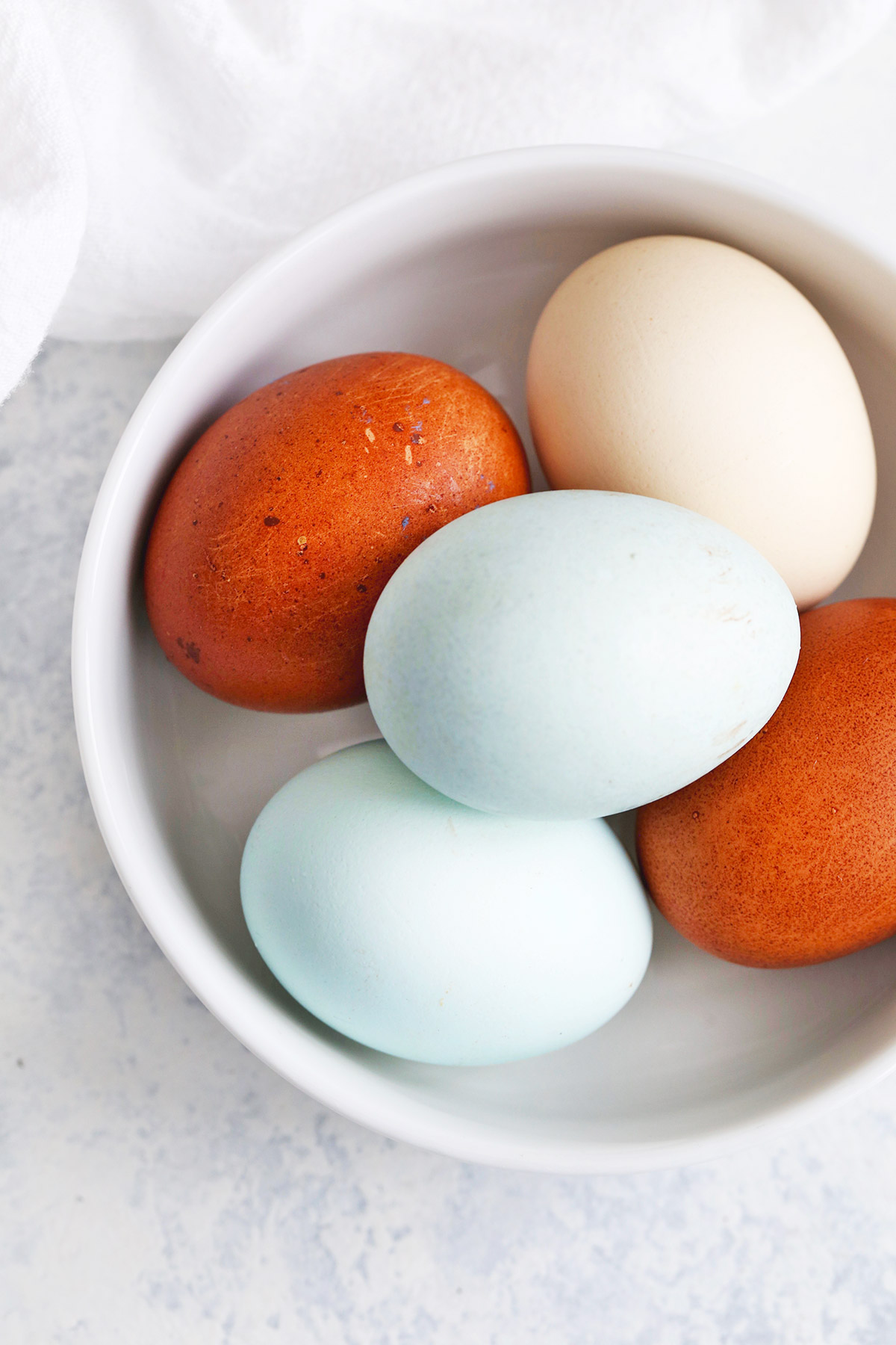 Overhead view of different colors of eggs in a white bowl.