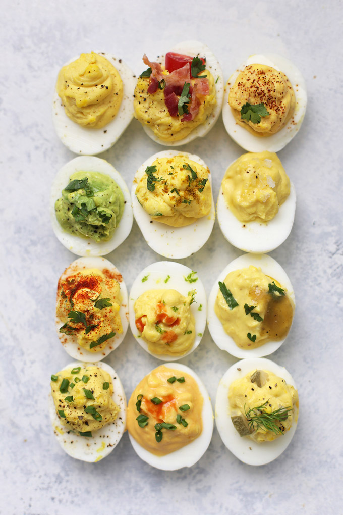 12 Different kinds of deviled eggs arranged on a light background from One Lovely Life