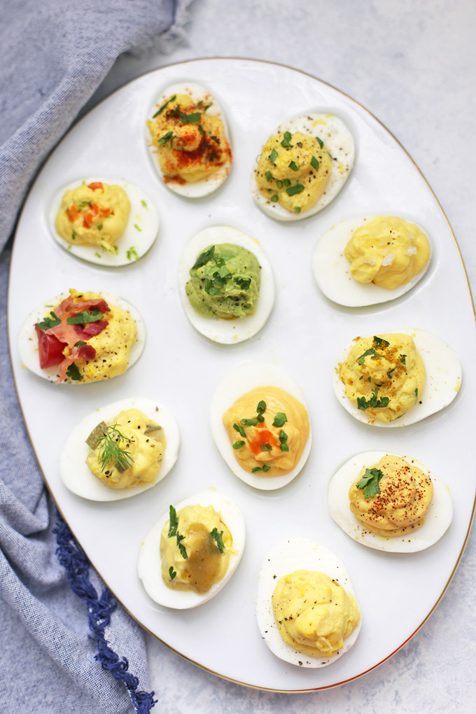 12 Different flavors of Paleo Deviled Eggs on an Egg Platter from One Lovely Life