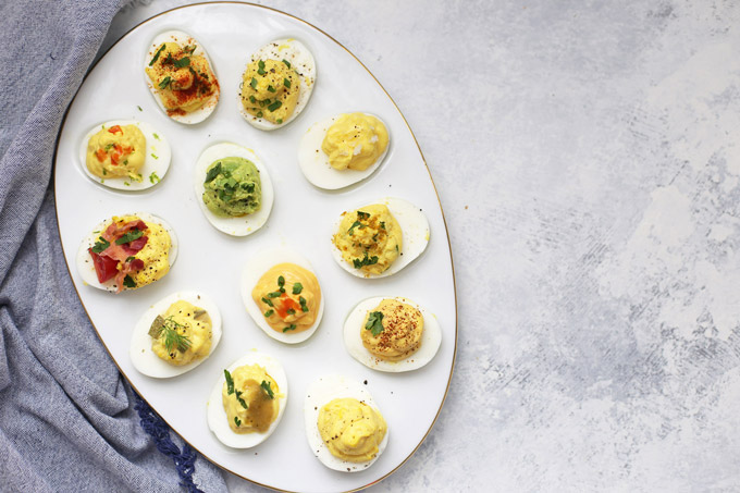 12 Different Kinds of Deviled Eggs arranged on an egg platter from One Lovely Life