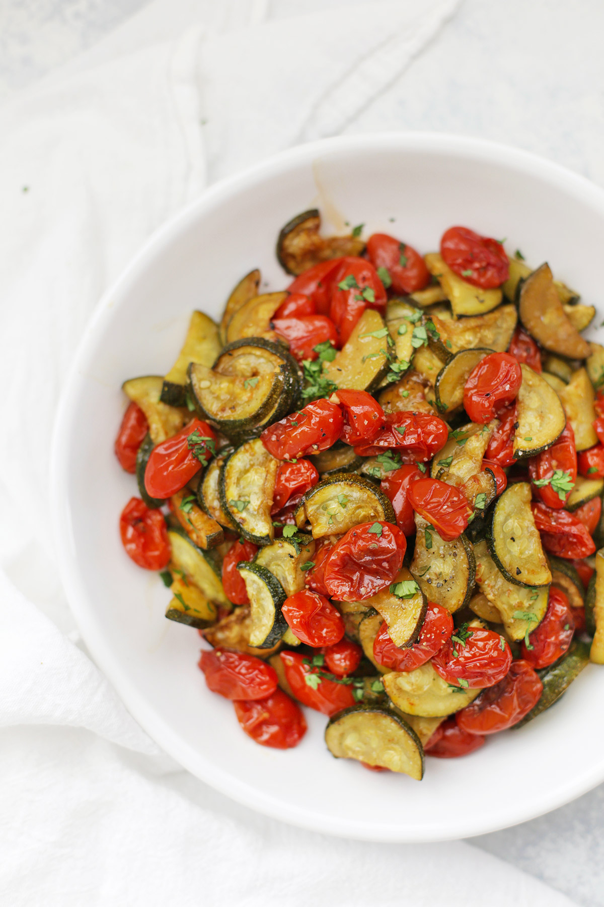 Close up view of a bowl of simply roasted zucchini and tomatoes with fresh herbs.