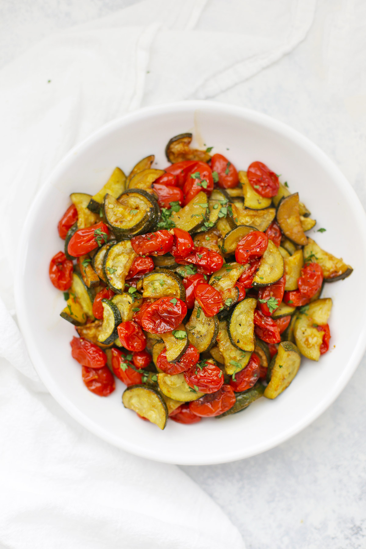 A bowl of simply roasted zucchini and tomatoes with fresh herbs.
