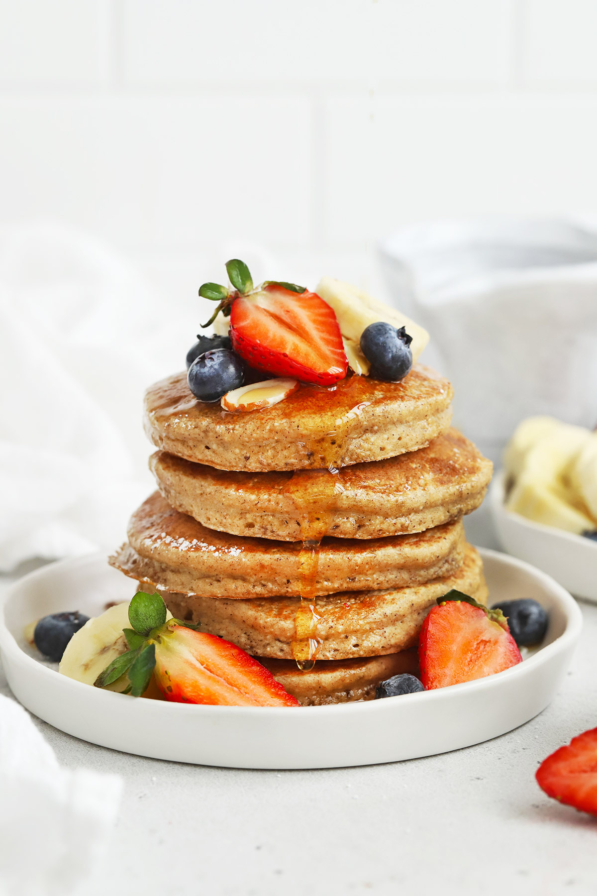 Front view of a stack of blender banana oatmeal pancakes topped with sliced bananas, fresh berries, and syrup.