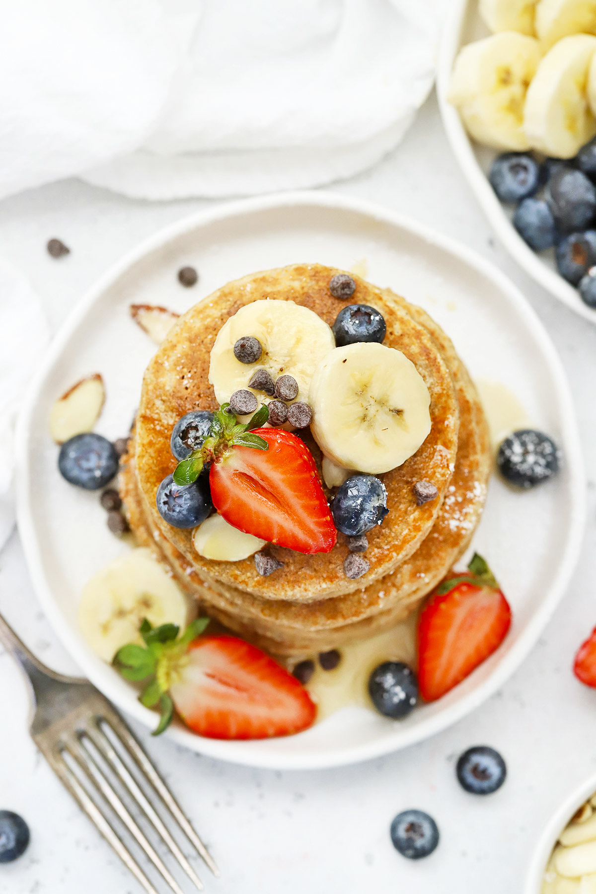 Overhead view of a stack of blender banana oatmeal pancakes topped with sliced bananas, fresh berries, and syrup.