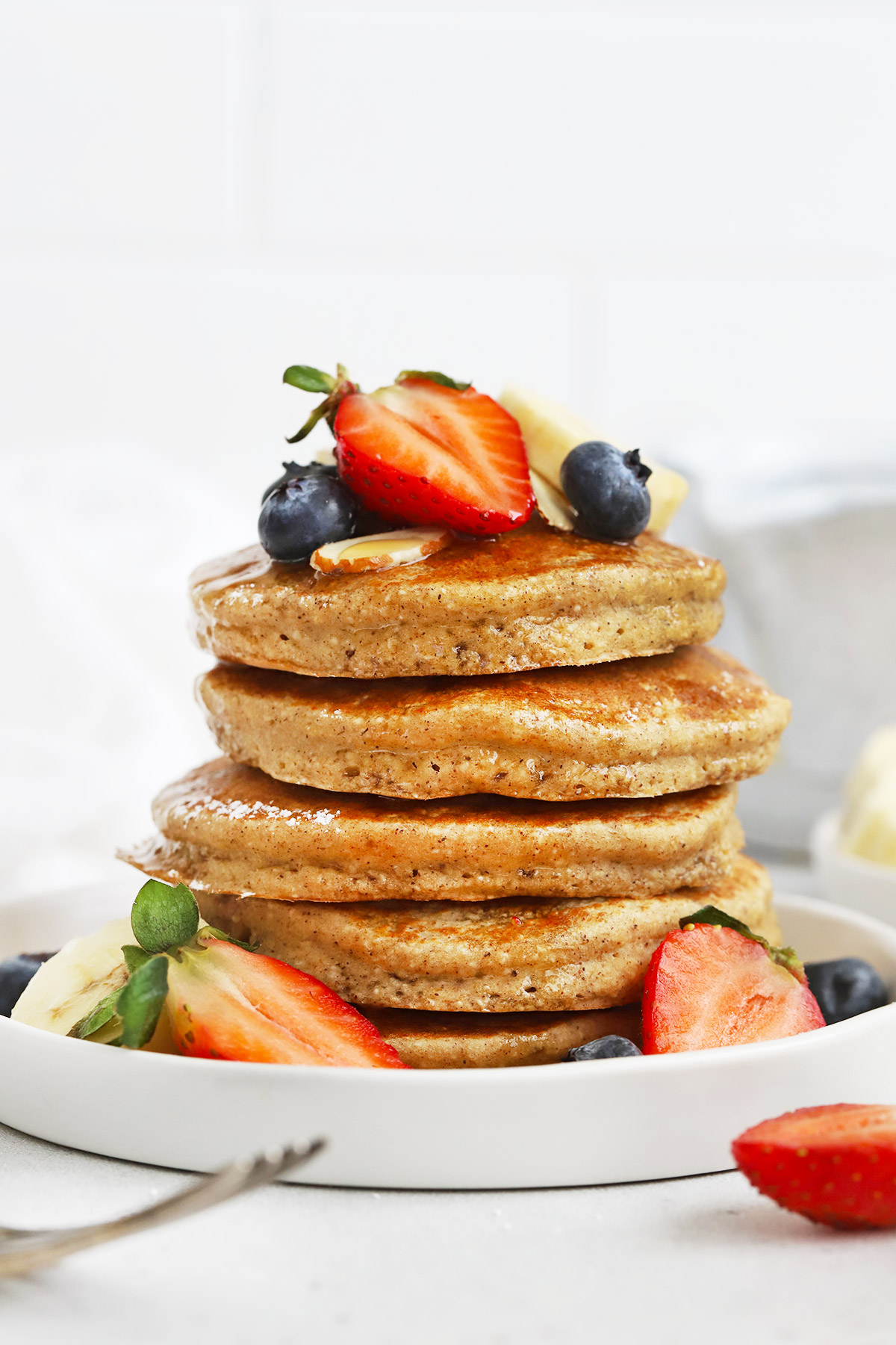 Close up Front view of a stack of blender banana oatmeal pancakes topped with sliced bananas, fresh berries, and syrup.