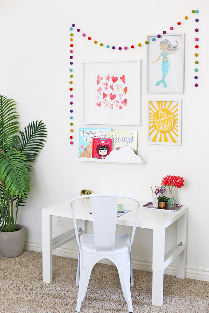 A fun gallery wall tops off her desk area. The desk is adjustable so it grows with your child!