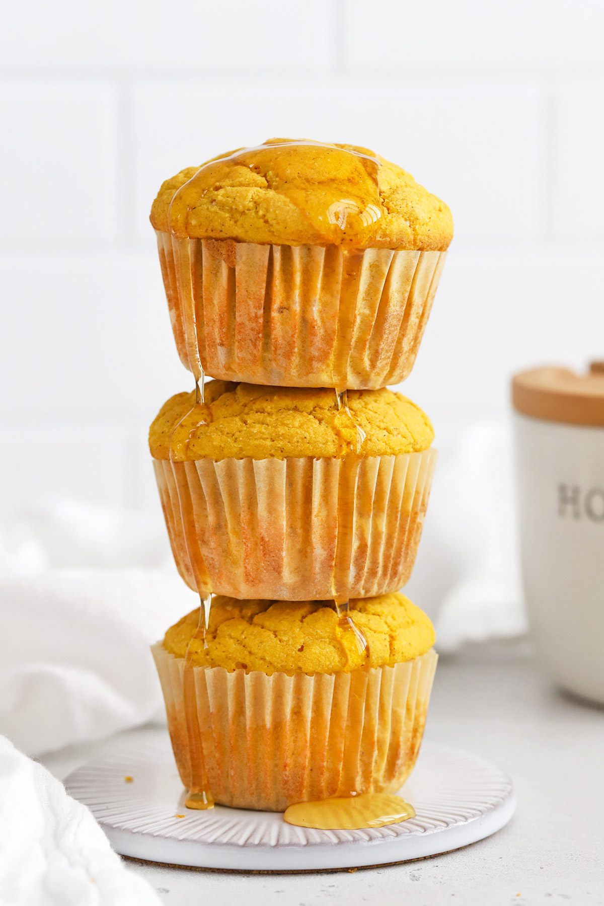 Three gluten-free pumpkin cornbread muffins drizzled with honey