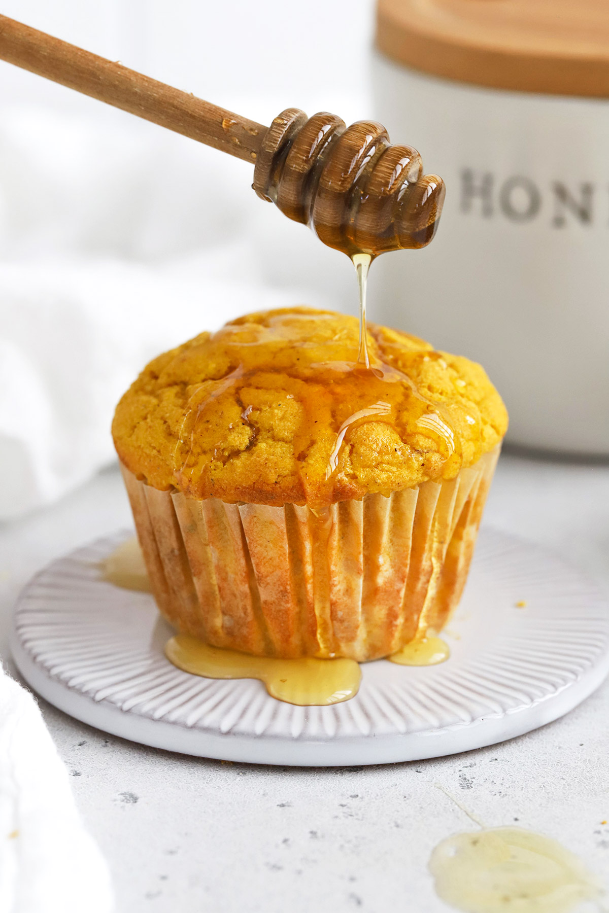 Gluten-Free cornbread muffin being drizzled with honey