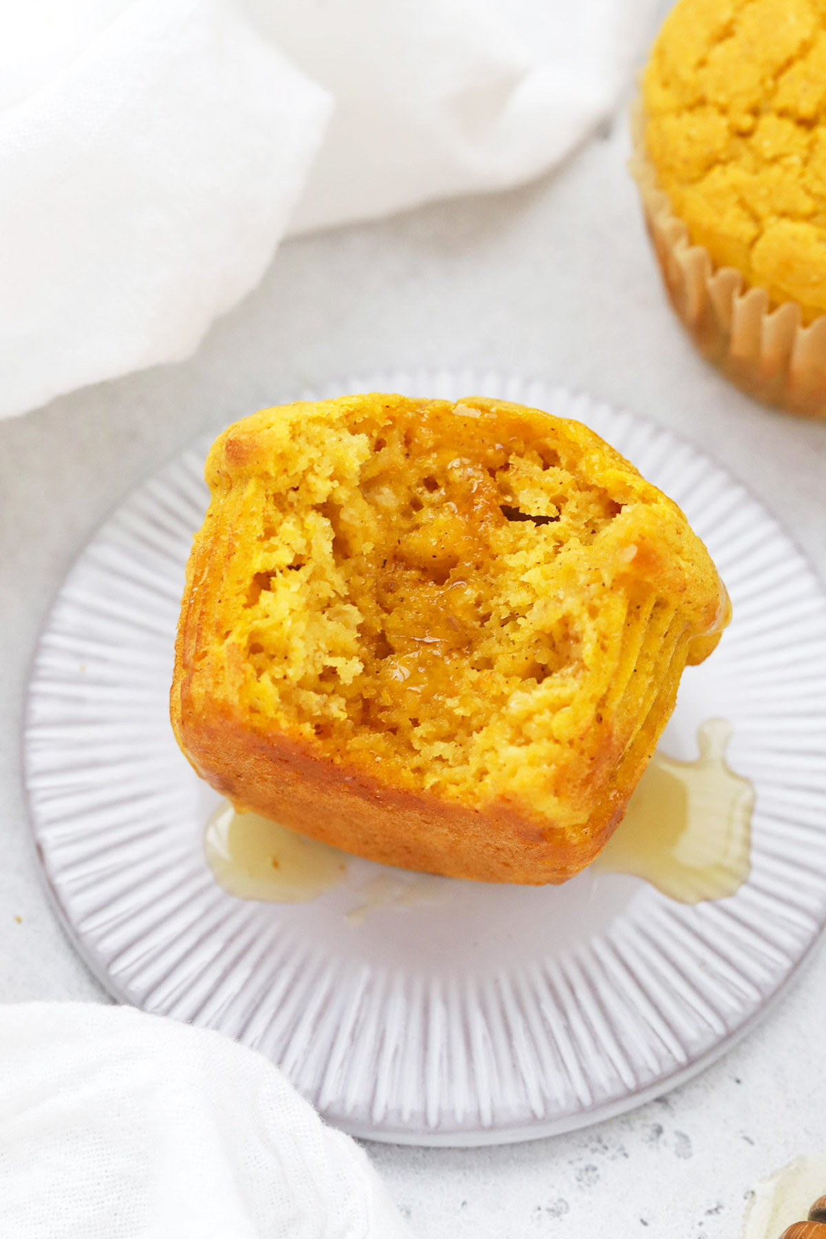 Front view of a gluten-free pumpkin muffin with a bite out of it, drizzled with honey