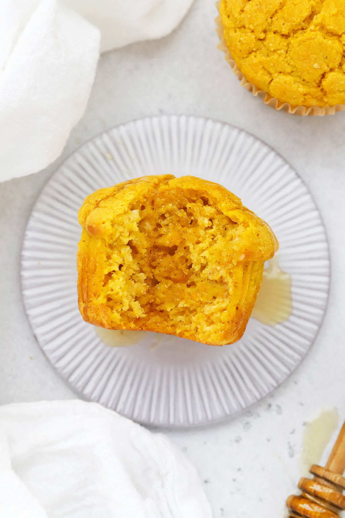 Overhead view of a gluten-free pumpkin muffin with a bite out of it, drizzled with honey