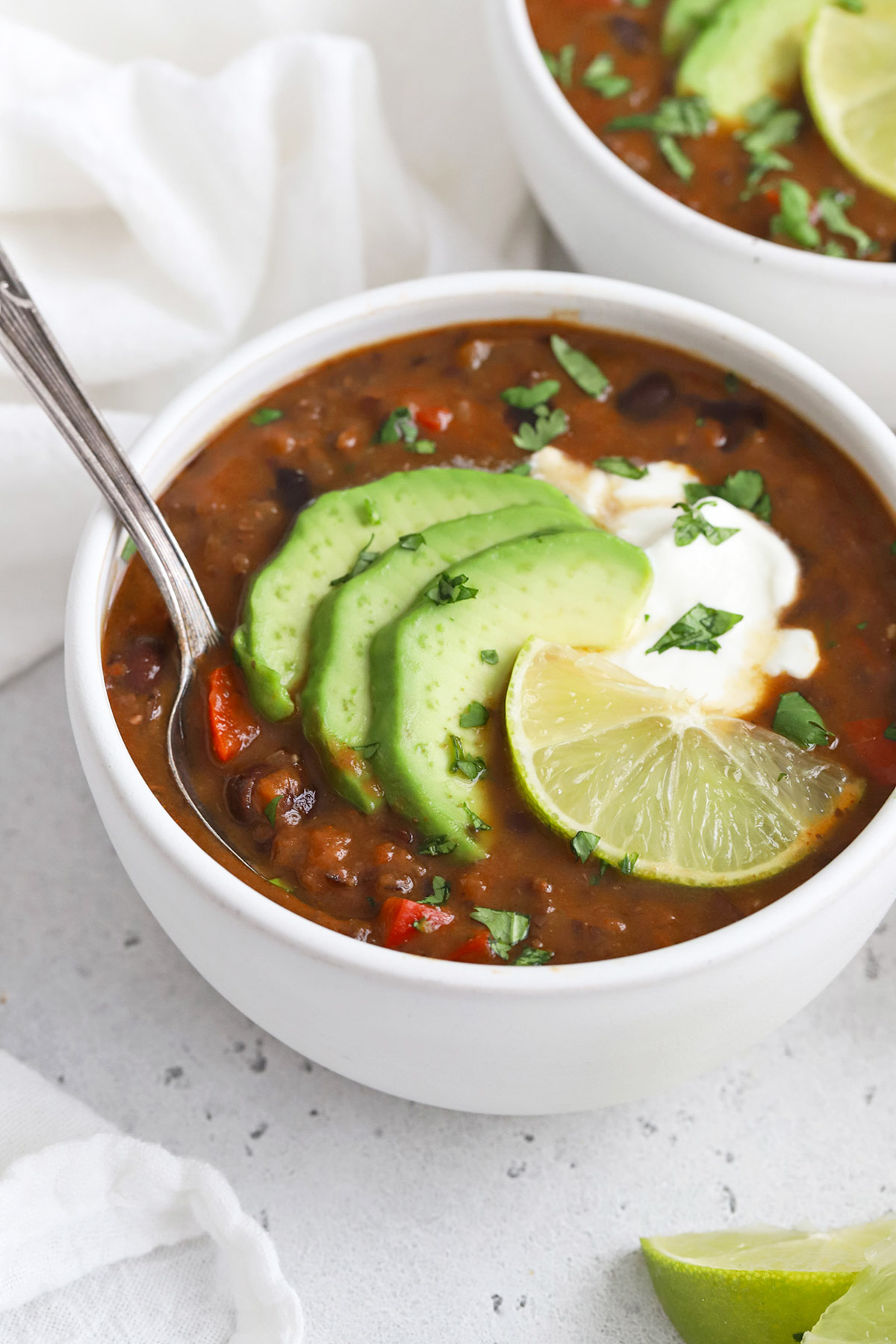 Front view of two bowls of vegan black bean soup topped with plain yogurt, sliced avocado, cilantro, and lime