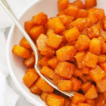Front view of cinnamon roasted butternut squash in a white bowl