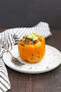 Front view of a Taco Quinoa Stuffed Pepper Jack O'Lantern on a plate with a fork.