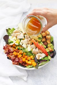 Pouring Apple Cider Vinaigrette over Fall Cobb Salad