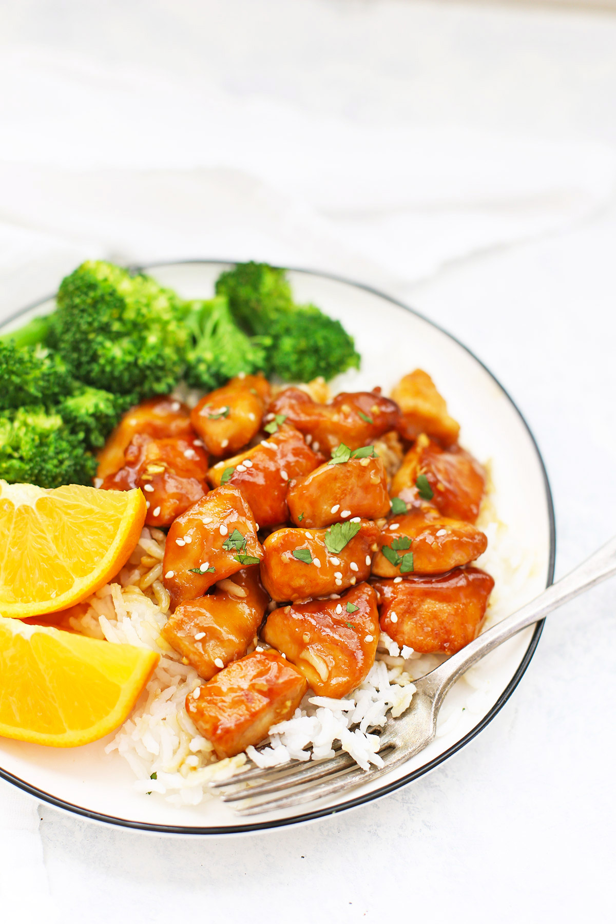 Front view of a plate with healthy orange chicken, rice, orange wedges and steamed broccoli on a white background