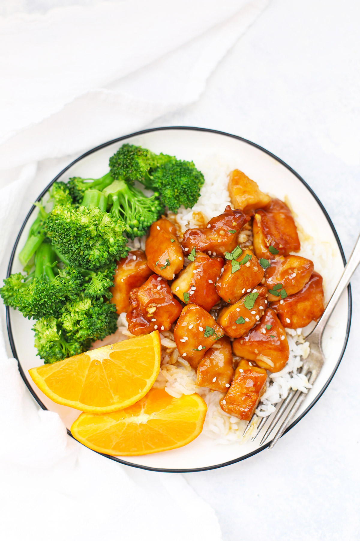 Overhead view of a plate with healthy orange chicken, rice, orange wedges and steamed broccoli on a white background