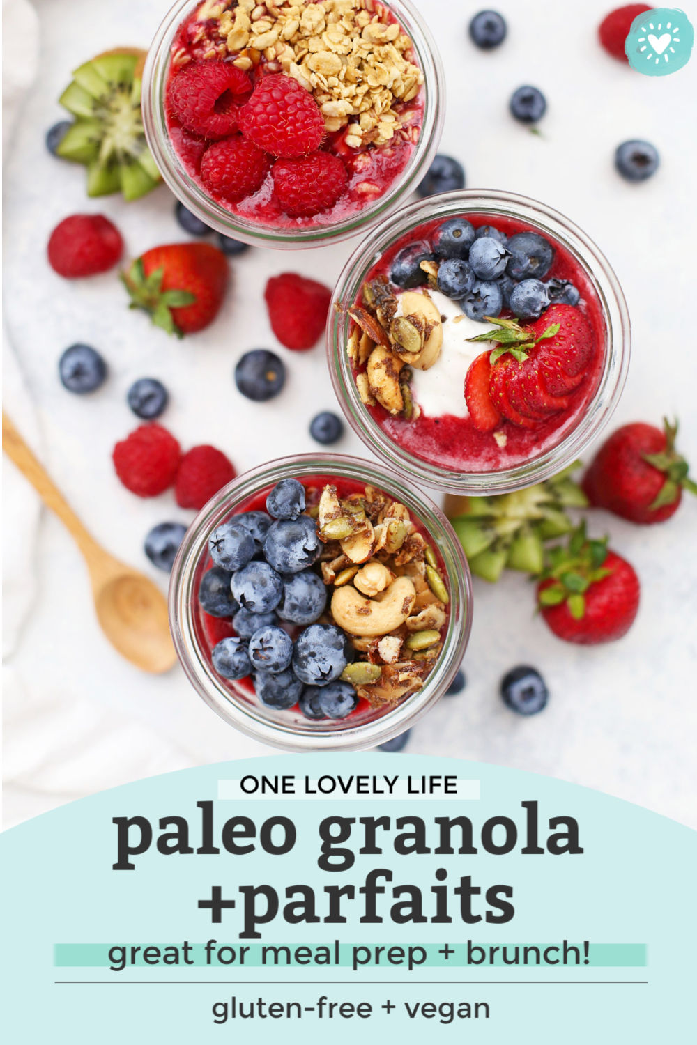 "Overhead view of jars of paleo granola parfait with fresh fruit, yogurt, and berry puree with text overlay that reads ""One Lovely Life. Paleo Granola + Parfaits--great for meal prep + brunch! Gluten-Free + Vegan."""