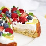 Close up view of Paleo Lemon Cake topped with Coconut Whipped Cream and Fresh Berries