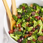 wooden salad tongs tossing Vegan Broccoli Salad with Poppy Seed Dressing in a white salad bowl