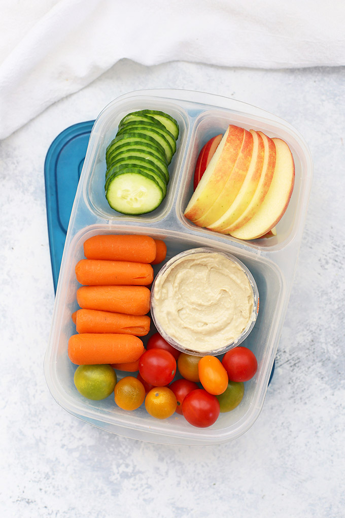 Easy Lunchboxes lunch box with blue lid packed with hummus, vegetables, and sliced apples.
