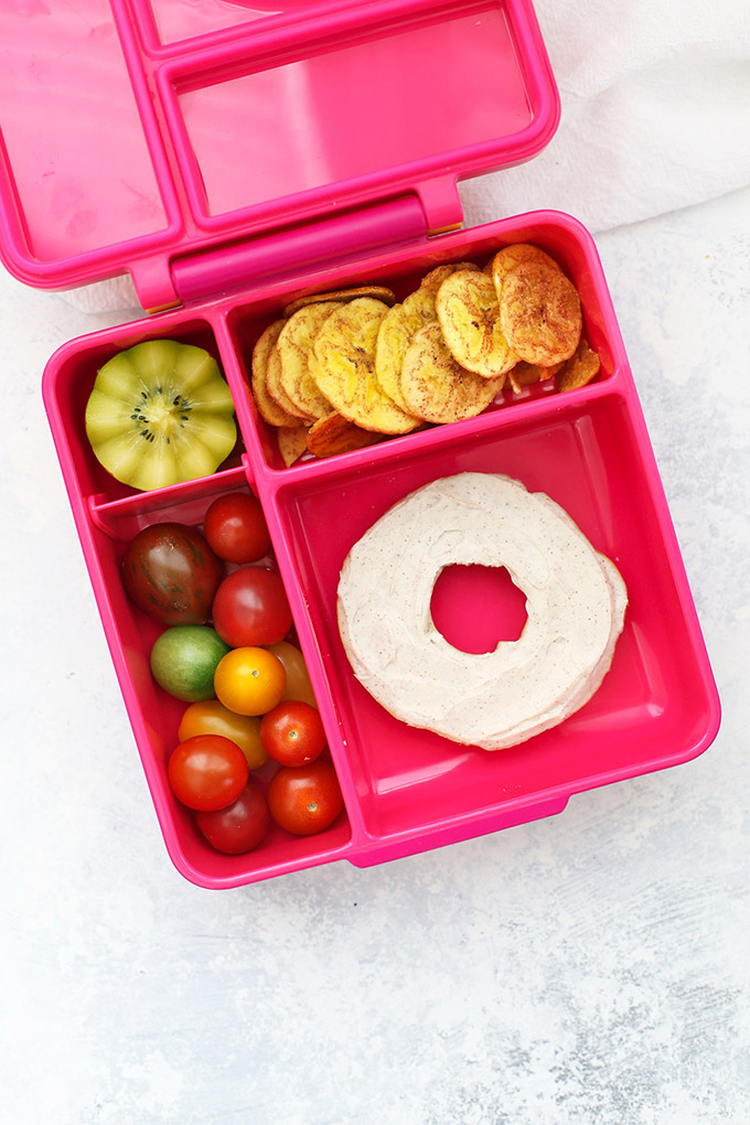 Healthy School Lunch Idea - Gluten Free Bagel with Cinnamon Almond Cream Cheese, Plantain Chips, Kiwi, and Baby Tomatoes in an Omie Box lunchbox.