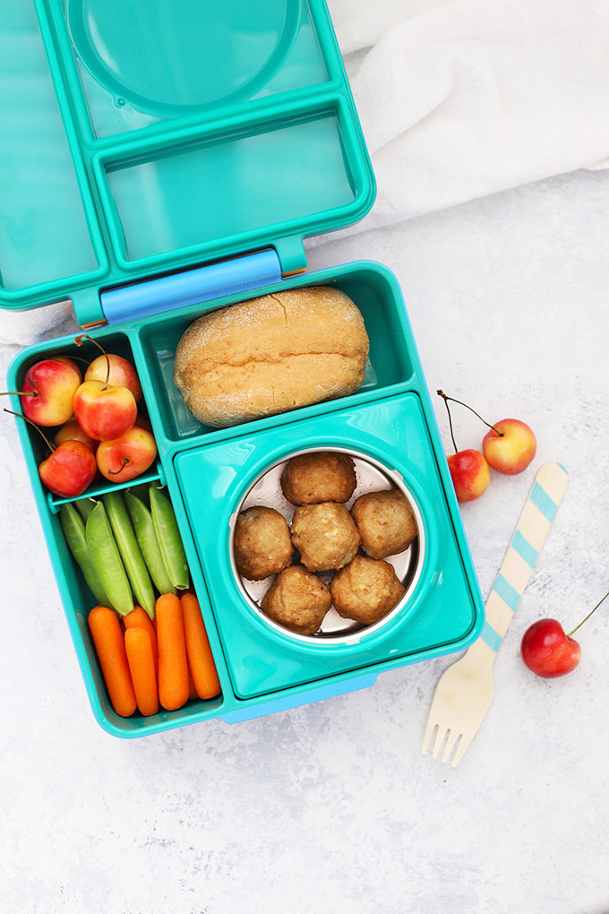 Healthy School Lunch Idea - Chicken Meatballs, Gluten Free Roll, Cherries, Peas, and Carrots in an Omie Box lunchbox.