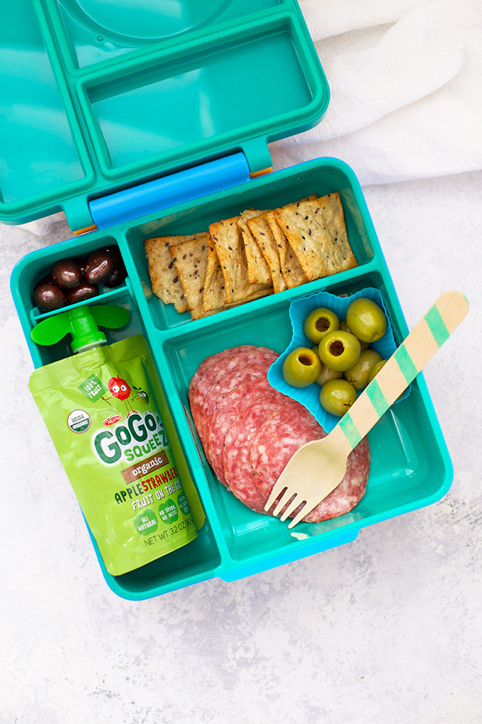 Healthy School Lunch Idea - Nitrate Free Salami, Green Olives, Applesauce Pouch, Chocolate Covered Almonds, and Gluten Free Crackers in an Omie Box lunchbox.