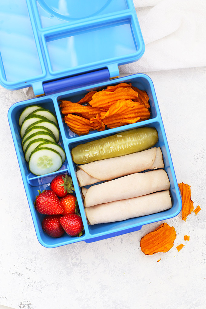 Healthy School Lunch Idea - Turkey Roll-Ups, Pickle, Strawberries, Sliced Cucumbers, and Sweet Potato Chips in an Omie Box lunchbox.