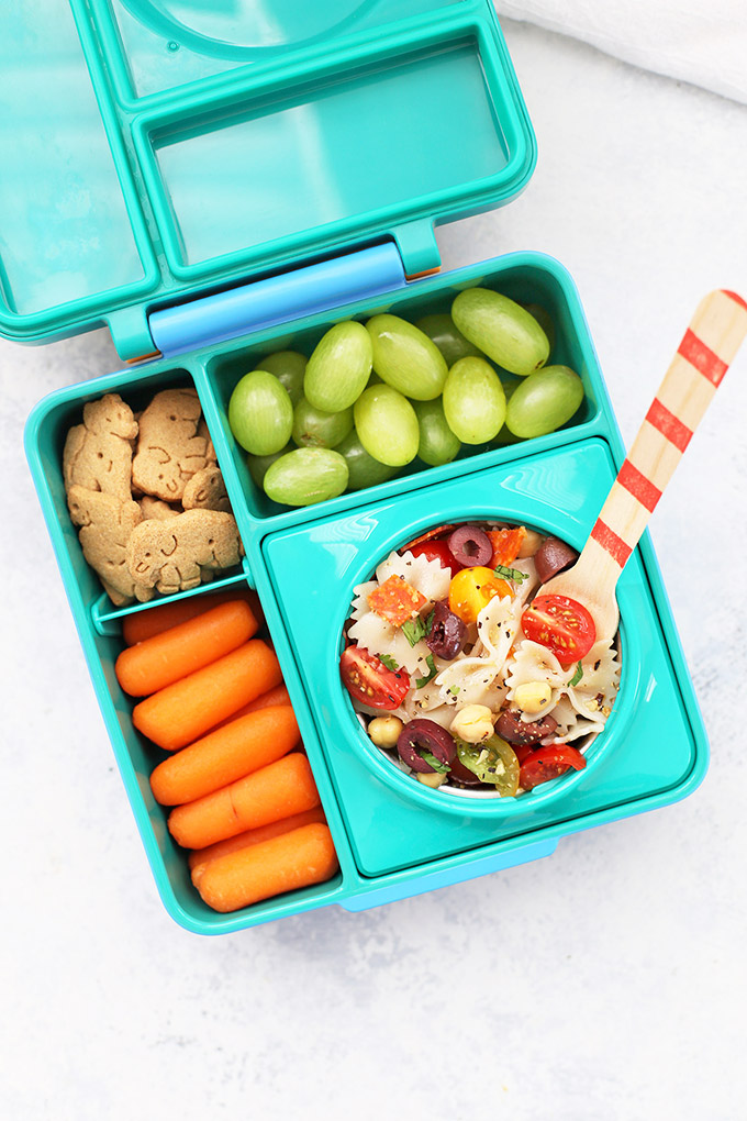Healthy School Lunch Idea - Gluten Free Pasta Salad, Baby Carrots, Gluten Free Animal Crackers, and Green Grapes in an Omie Box lunchbox.