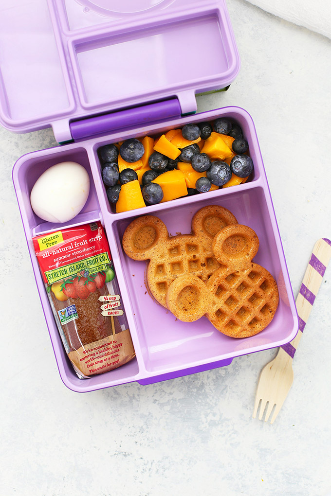 Healthy School Lunch Idea - Almond Flour Waffles, Fruit Leather, Mango and Blueberries, Boiled egg in an Omie Box lunchbox.