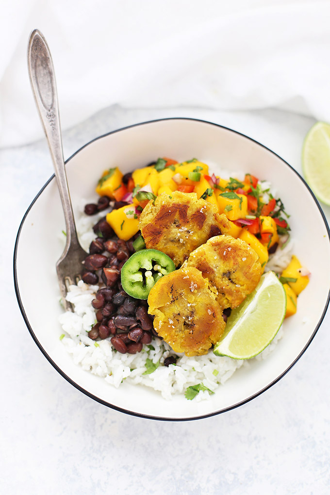 Vegan Plantain Burrito Bowl with Cilantro Lime Rice, Cuban Black Beans, Crispy Plantains, and Fresh Mango Salsa. Lime Wedge and Jalapeño Garnish.
