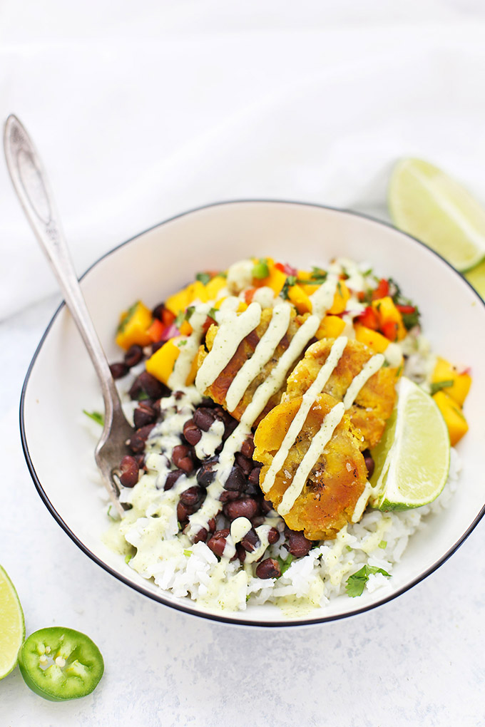 Vegan Plantain Burrito Bowl with Cilantro Lime Rice, Cuban Black Beans, Crispy Plantains, and Fresh Mango Salsa with Tomatillo Ranch Dressing Drizzled on Top. Lime Wedge and Jalapeño Garnish.