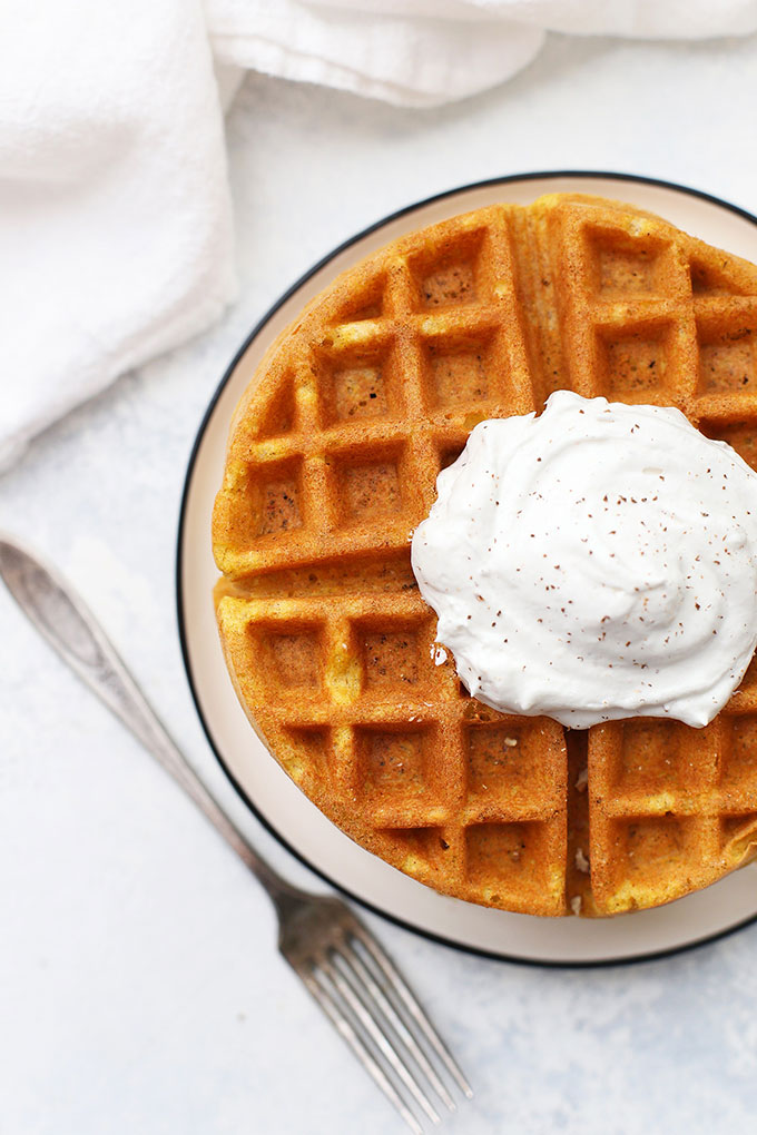 Stack of Almond Flour Pumpkin Waffles with coconut whipped cream and cinnamon