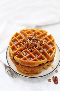 Stack of Almond Flour Pumpkin Waffles with pecans and maple syrup.