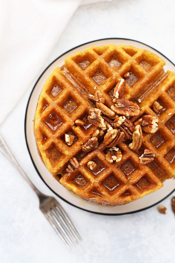 Overhead view of a Stack of Almond Flour Pumpkin Waffles with pecans and maple syrup.