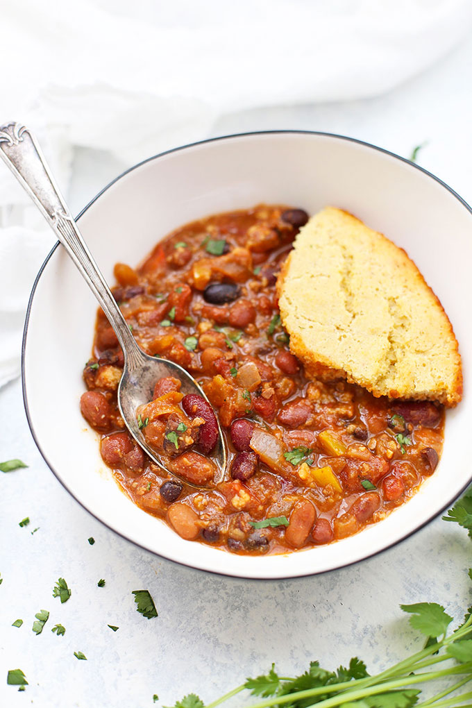 Front view of chili and cornbread in a bowl, with a spoon