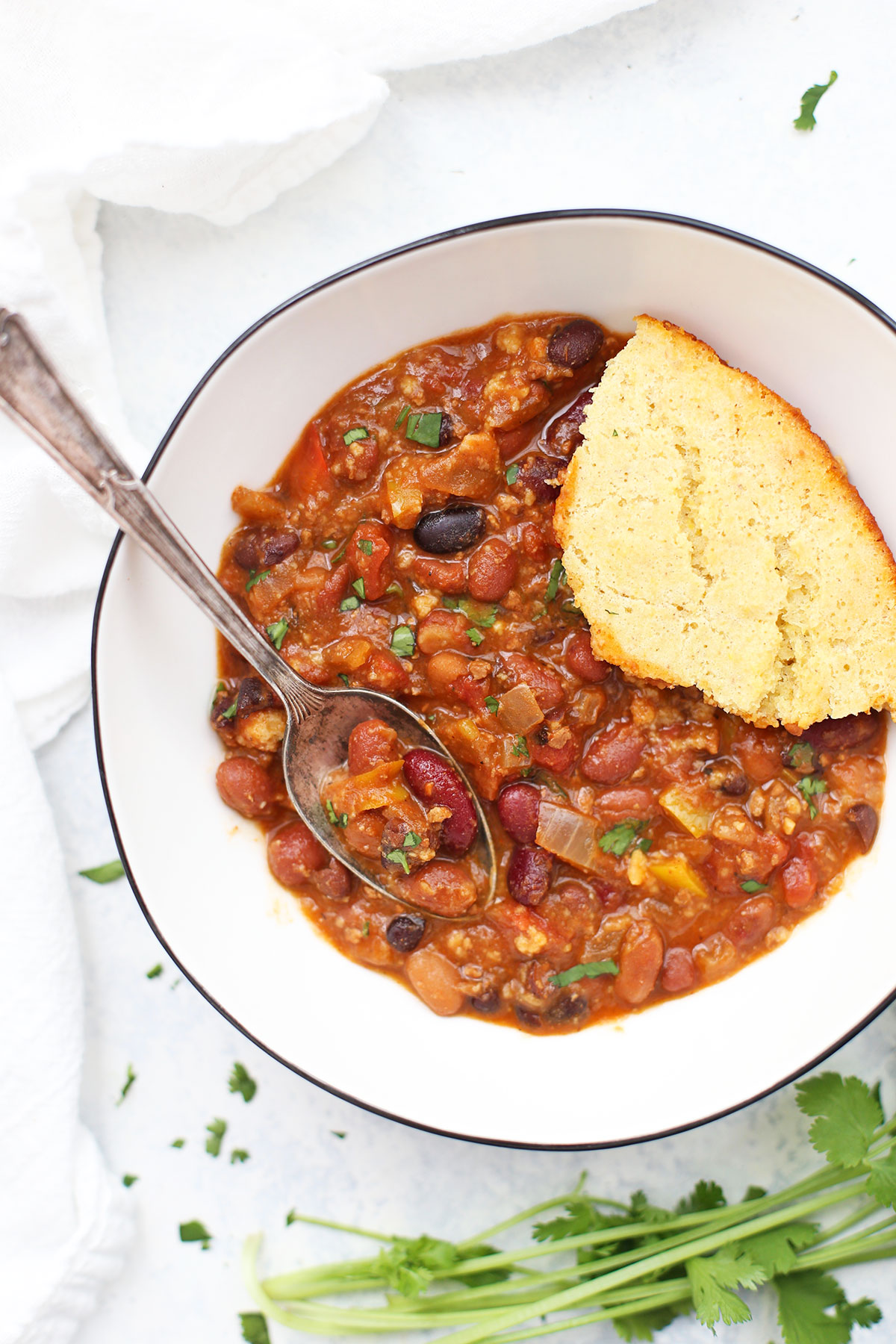 Close up view of chili and cornbread in a bowl with spoon inside