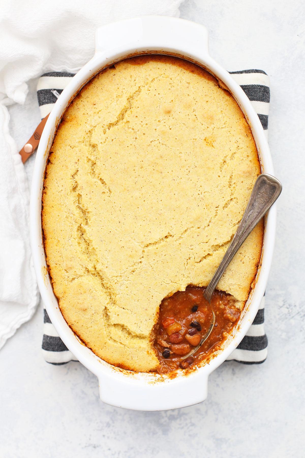 Overhead view of chili cornbread pot pie with spoon in it