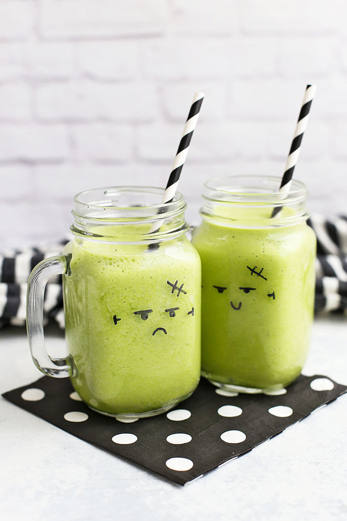 Two green smoothies with monster faces drawn on the cups.