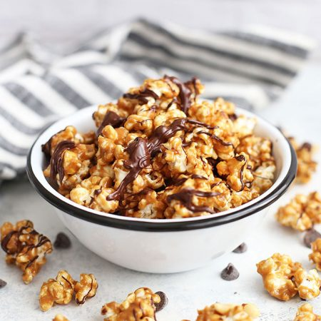 Front view of a bowl of vegan peanut butter popcorn with chocolate drizzle