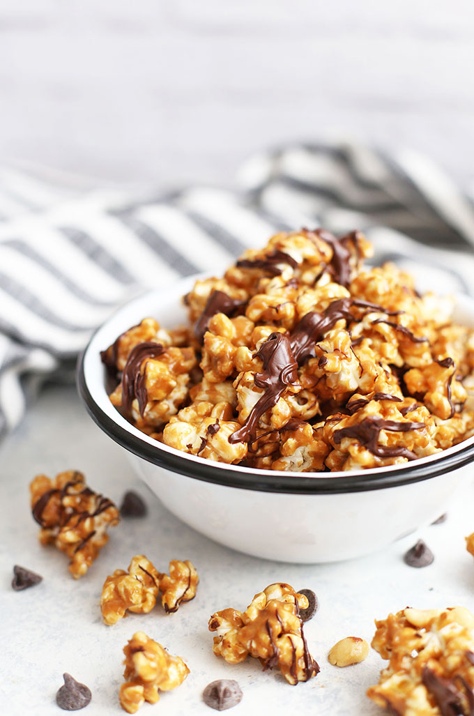 Close up front view of a bowl of vegan peanut butter popcorn with chocolate drizzle