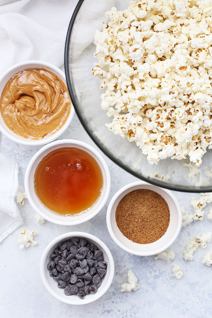 Ingredients for Vegan Peanut Butter Popcorn with Chocolate Drizzle - Large bowl of popped popcorn, and small bowls of natural peanut butter, agave syrup, coconut sugar, and chocolate chips