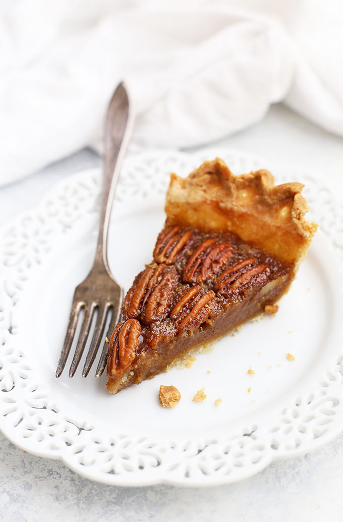 Side view of a slice of pecan pie on a white doily plate with a fork next to it.