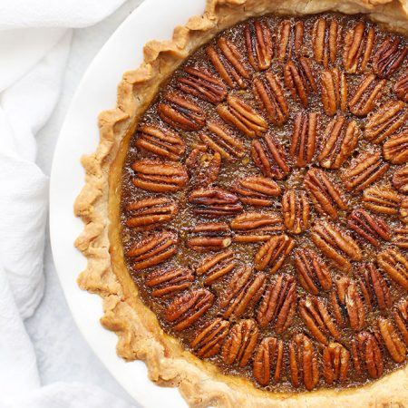 Overhead view of a gluten free pecan pie in a white ruffled pie dish.