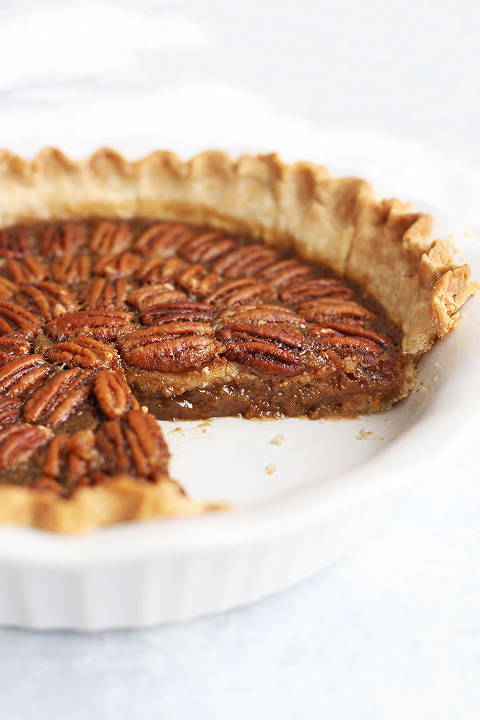 Front view of a pecan pie with a slice removed.