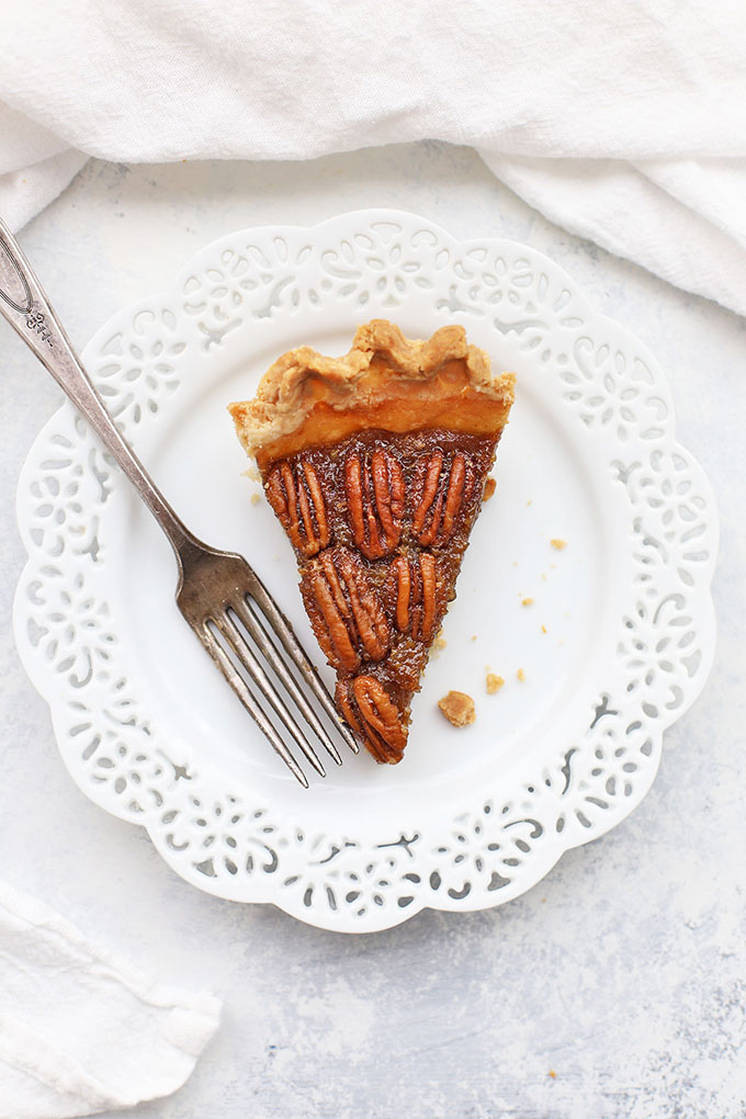 Overhead view of a slice of gluten free pecan pie on a white doily plate.