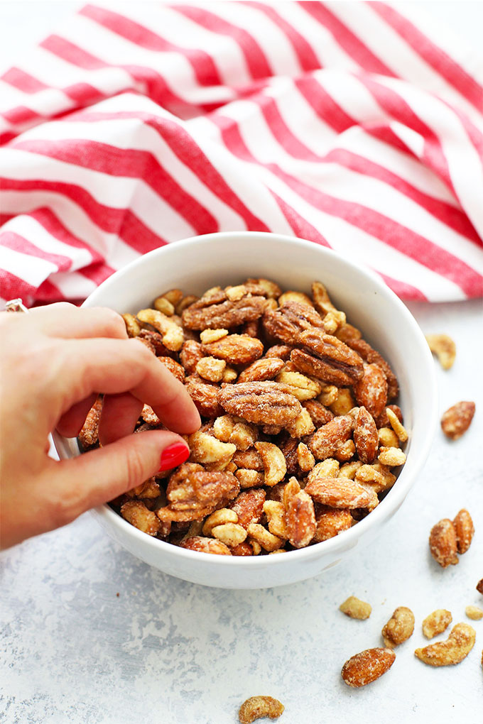 Front view of a bowl of spiced candied nuts with red and white striped dishtowel in the background.