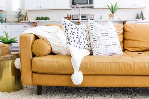 Article Sven Charme Tan Leather Sofa with White pom blanket and black and white throw pillows