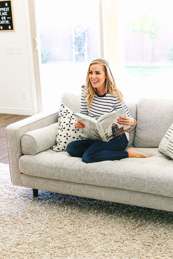 Emily of One Lovely Life sitting with a book on Article Sven Sofa in Birch Ivory